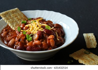 Close up of homemade slow cooked  Bean Chili Bowl against black background, selective focus