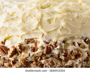 Close up of a homemade southern hummingbird cake showing icing and pecans