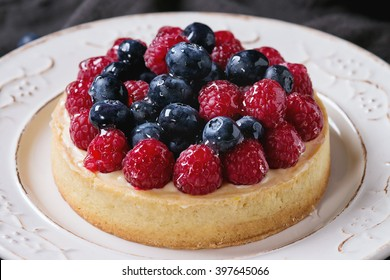 Close up of Homemade tart with custard, fresh raspberries and blueberries, served on white vintage plate on textile napkin over old wooden table. Dark rustic style