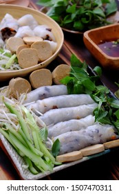 Close up homemade Vietnamese vegan rolled steamed rice pancake or banh cuon in plate with herb and sauce on wooden background