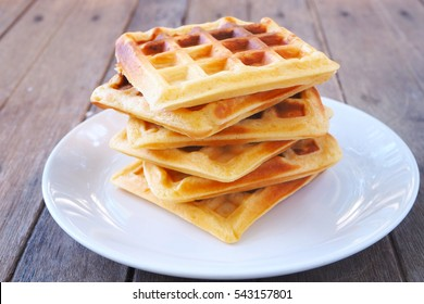 Close up of homemade waffles on a wooden background.