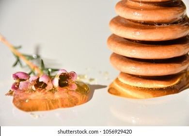 Close up of honey and dipper on a white background, manuka honey