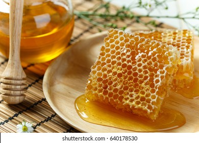 Close up honeycomb with honey in glass jar on the bamboo placemat