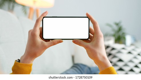 Close up of horizontal black smartphone with blank screen in woman hands. Mobile phone with blank copy space screen for your text