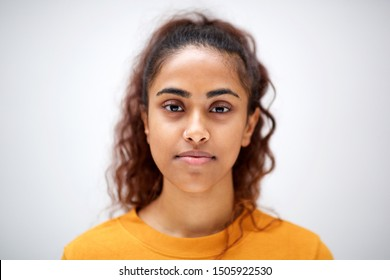 Close up horizontal front portrait of attractive young indian woman with serious expression on face