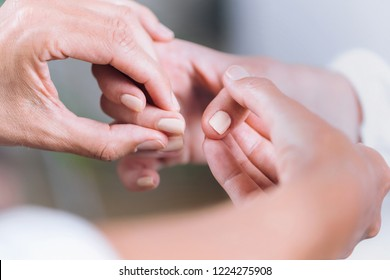 Close up horizontal image of female hands performing muscle testing at Theta healing session. Therapist and patient sitting and wearing white clothes. Energy healing concept