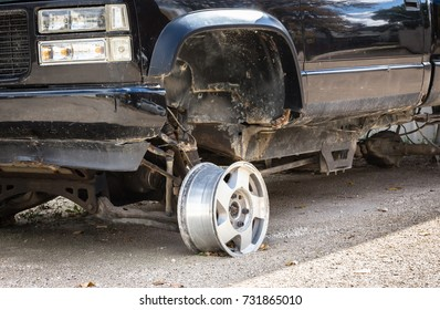 close up horizontal image of the front end of a black truck with only a metal rim on the wheel with no tire.