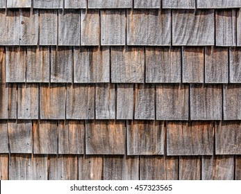 Close up of horizontal image of gray and brown wooden shingles roof with frost for background texture