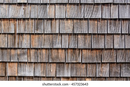 Close up of horizontal image of gray and brown wooden shingles roof with frost (rime) for background texture