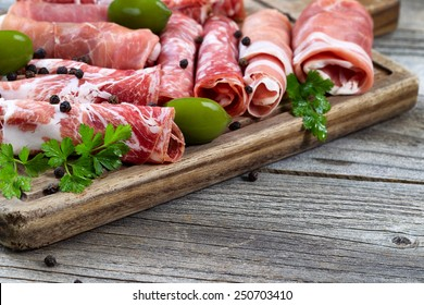 Close up horizontal image of various meats on serving board with ham, pork, beef, parsley, and olives on rustic wood. Focus on side part of serving board and first row of meat.