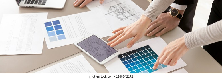 Close up horizontal photo of colleagues interior designers working with color swatches palette and blueprint, planning discussing together creative occupation concept banner for website header design