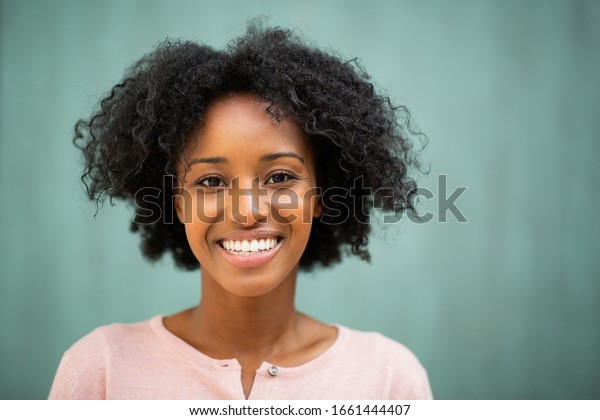 Close up horizontal portrait beautiful young black woman smiling by green background
