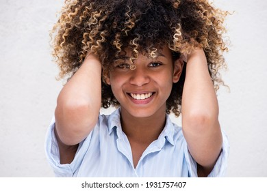 Close up horizontal portrait smiling young African american teen girl with hand in curly hair