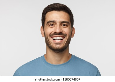 Close up horizontal shot of handsome smiling broadly unshaven young man in blue tshirt laughing out loud