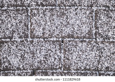 Close up of horizontally tiled surface covered with first snow. Abstract background