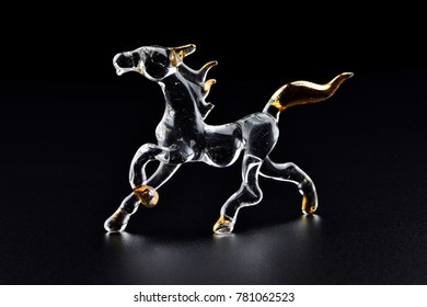Close up horse made from glass with a black background.