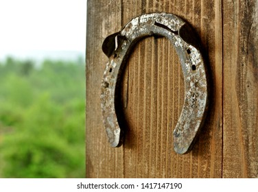 Close up of an horseshoe (clout) hanged on an wooden pillar with copy text.