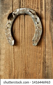 Close up of an horseshoe (clout) on wooden background. Vertical, copy space text