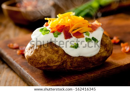 Close up of a hot baked potato topped with sour cream, bacon, green onions and cheddar cheese.