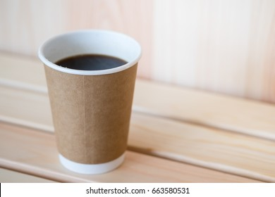 Close up of hot black coffee americano paper cup on on wooden table.