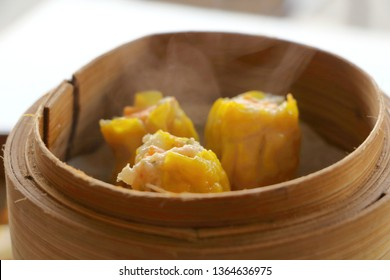 Close up hot Cantonese Shumai (Siu Mai) Dim Sum, shrimp & pork Chinese steamed dumplings recipe wrap by yellow wonton wrapper (Kanom Jeeb in Thai) in bamboo basket in dim sum set have smoke