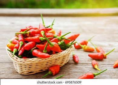 Close up of hot chili peper on basket and wooden background with sunlight, copy space concept.