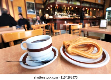 Close up of hot chocolate drink servd with Spanish doughnut (Churros) in outdoor cafe in Madrid, Spain.