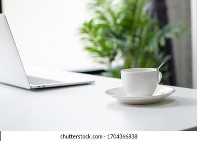 Close up of a hot coffee cup for a young business man on a white desk with morning sunshine at home.