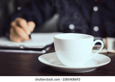 close up hot cup of coffee and soft businessman working soft background