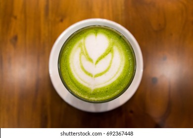 Close up hot greentea matcha latte art on wooden table