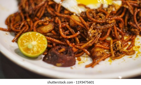 Close up of hot and spicy asian style fried noodles or mee goreng in malay with cuts of lime serving on the plate. Selective focus