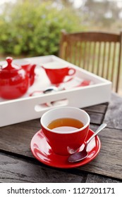Close up of hot tea on wooden table at outdoor. Complete tea set at background