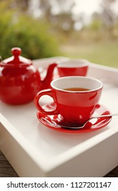 Close up of hot tea and tea pot on white tray. Outdoor garden background.