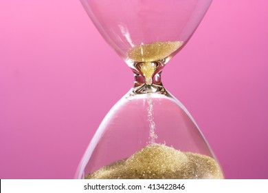 Close up of hourglass against pink background