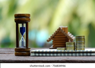 close up hourglass, stack of coins, notebook and toy house on old wood table, saving money for building and manage time for success business concept