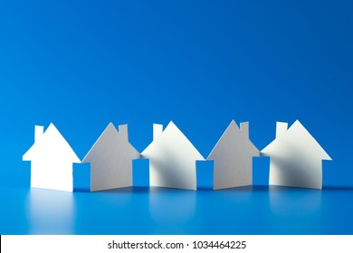 close up of house cut out of paper on blue background
