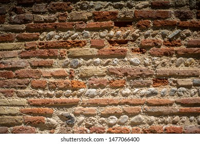 a close up of a house wall south of France. House nicknamed bastide. Wall of bricks and stones arranged in geometric way