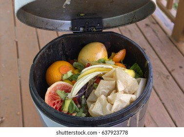 Close up of a household metal compost bin a house deck with the lid lifted up showing vegetable waste and compostable parchment paper decomposing inside