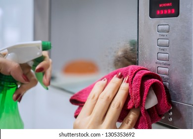 Close up of housemaid hands using a spray detergent to clean microwave in the kitchen. Shot at home