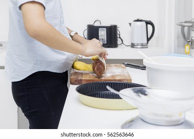 Close up of housewife rolling pie dough on the wooden board while standing in the kitchen