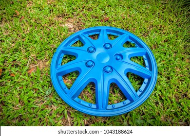 Close up of a hubcap isolated on grass background, selective focus.