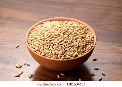 Close up of Hulled Barley in a Earthen Bowl on Wooden Background