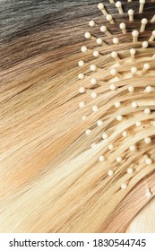 Close up of human hair base color palette, hair samples chart, with a wooden comb