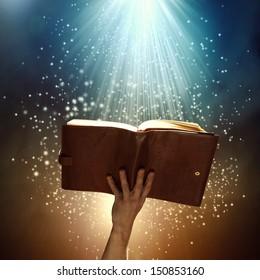 Close up of human hand holding saint book