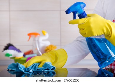Close up of human hand with protective gloves cleaning induction hob with rag. Cleaning supplies in background