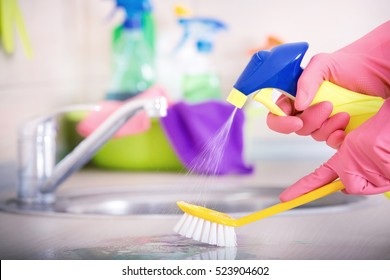 Close up of human hand in protective gloves holding scrubbing brush and spray bottle and washing kitchen counter top. Sink and cleaning supplies in background