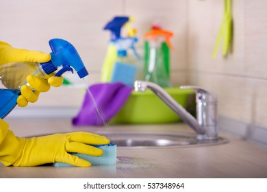 Close Up Of Human Hand In Protective Gloves Holding Sponge And Spray Bottle  And Wiping Kitchen