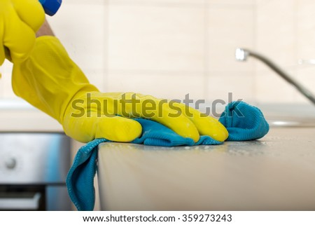 Close up of human hand in protective gloves holding mop and spray bottle and wiping kitchen countertop