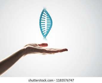 Close of human hand showing DNA molecule on gray background