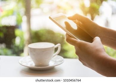 Close up of human hand using smart phone for internet shoping online in the morning at coffee shop. business ecommerce concept